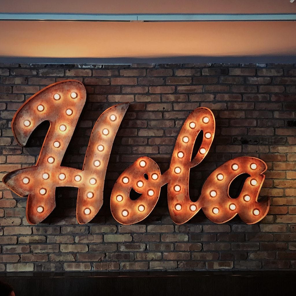 """""""Hola"""" written in lights on a brick wall."""